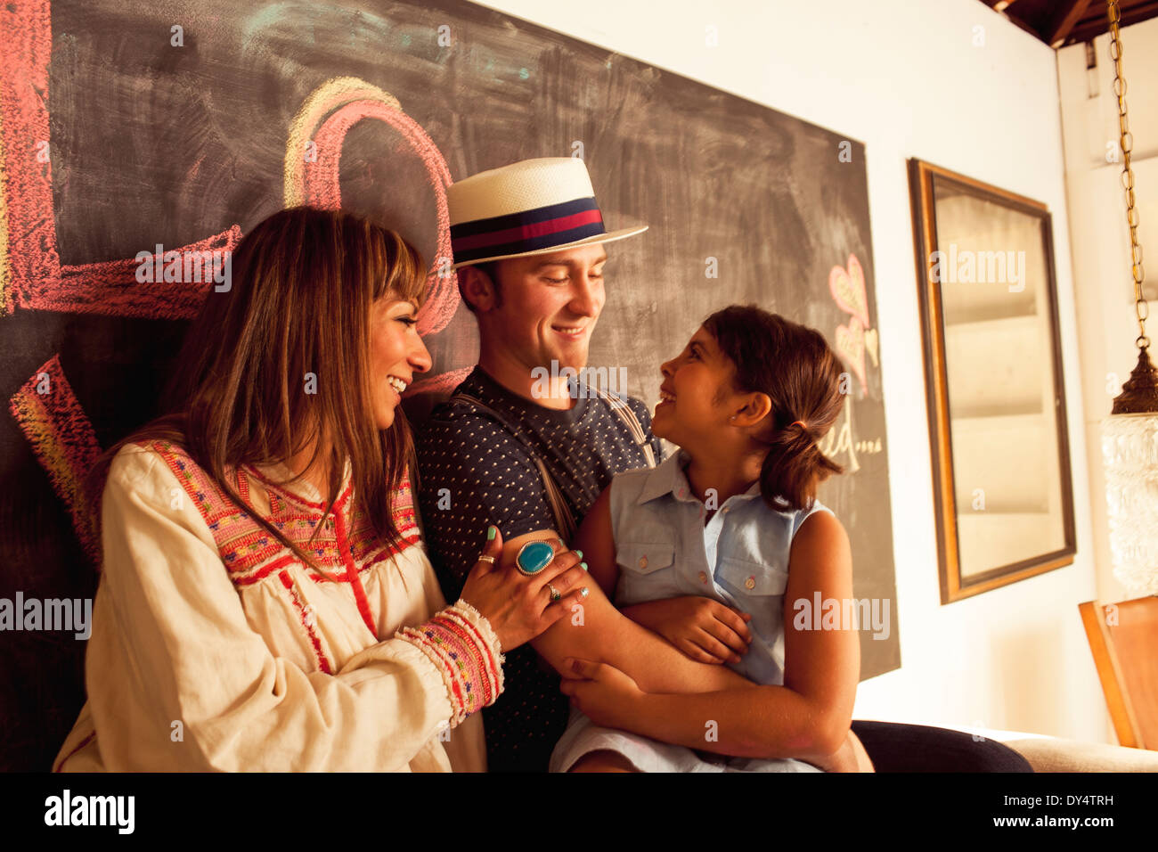 Father, mother and daughter talking and smiling - Stock Image