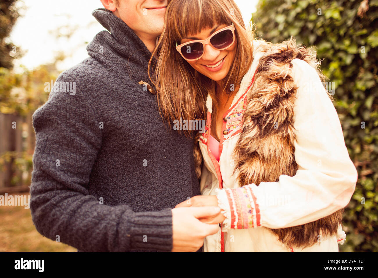 Couple holding hands laughing, cropped - Stock Image