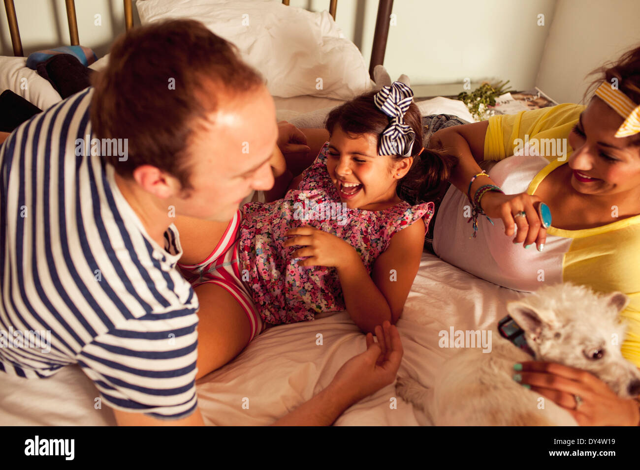Father and mother on bed tickling daughter - Stock Image