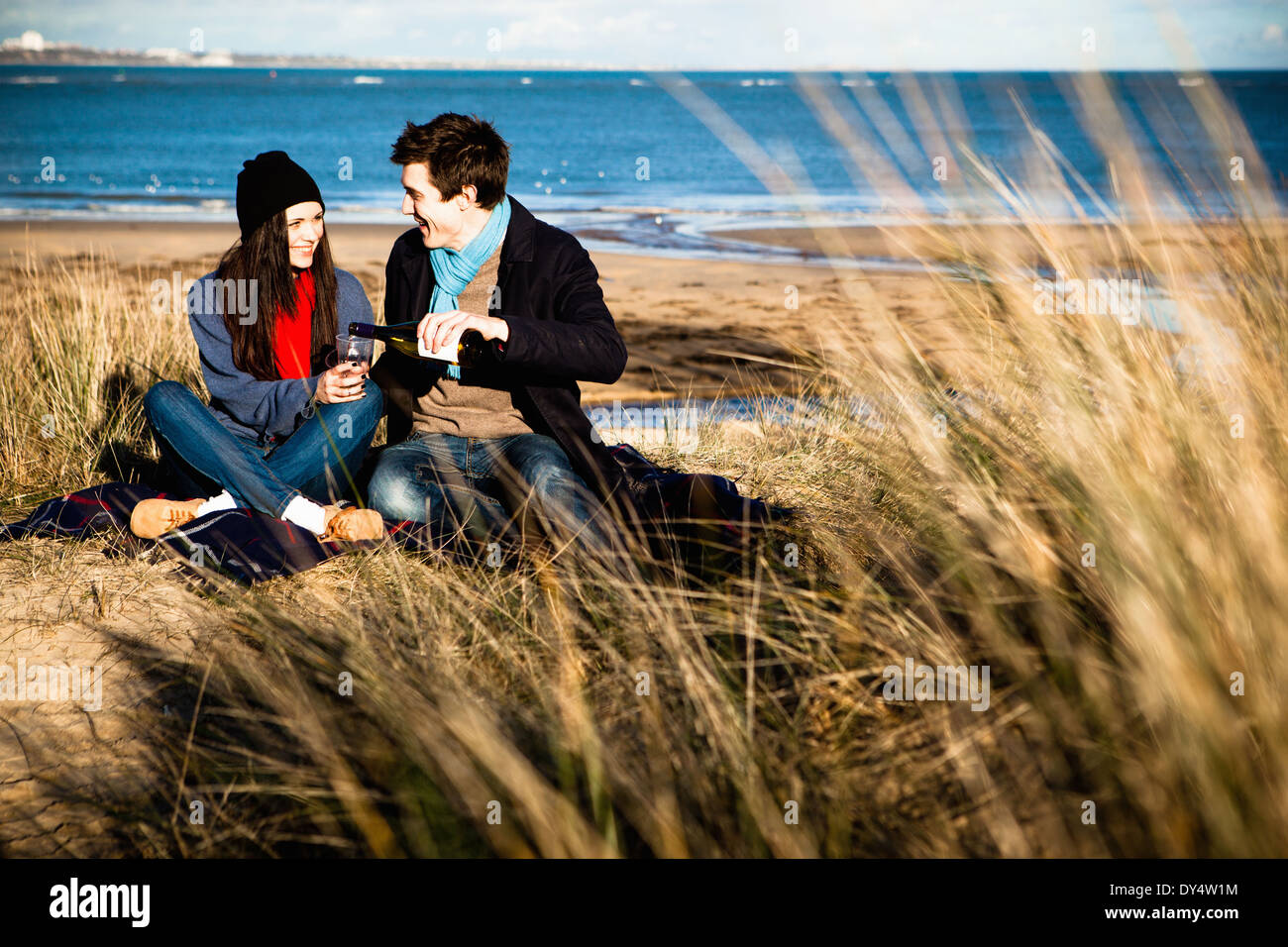 Couple celebrating with white wine on beach, Bournemouth, Dorset, UK - Stock Image