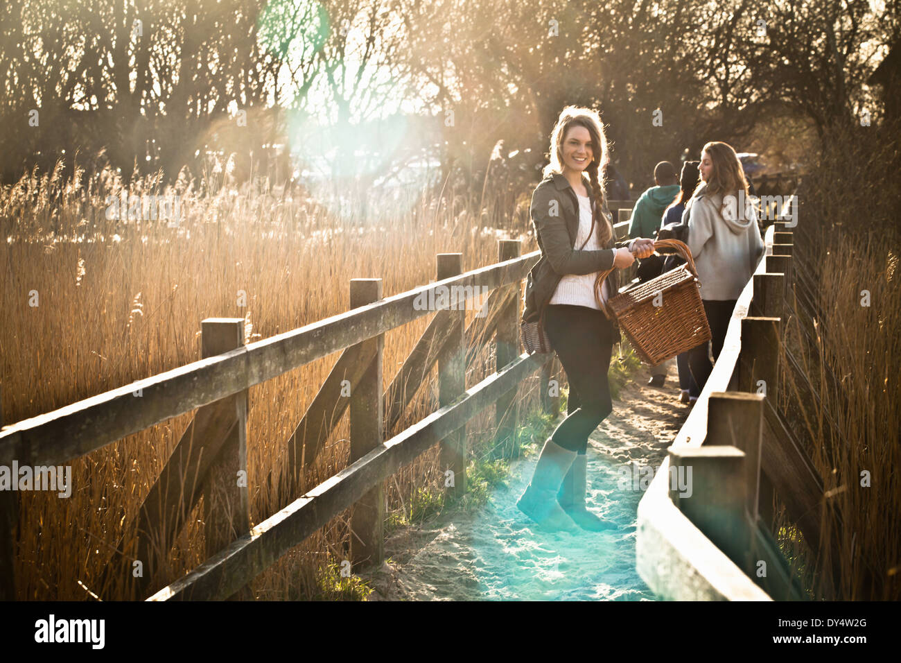 Young adult friends carrying picnic basket over footbridge - Stock Image