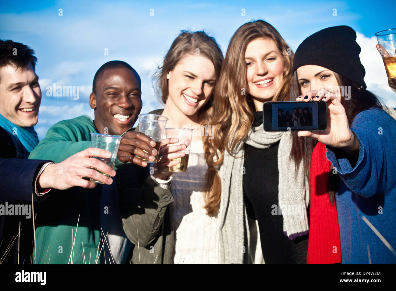 Young adult friends toasting with white wine and taking selfie - Stock Image