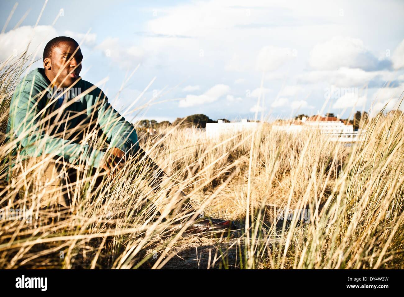 Young man sitting in sand dunes, Bournemouth, Dorset, UK - Stock Image
