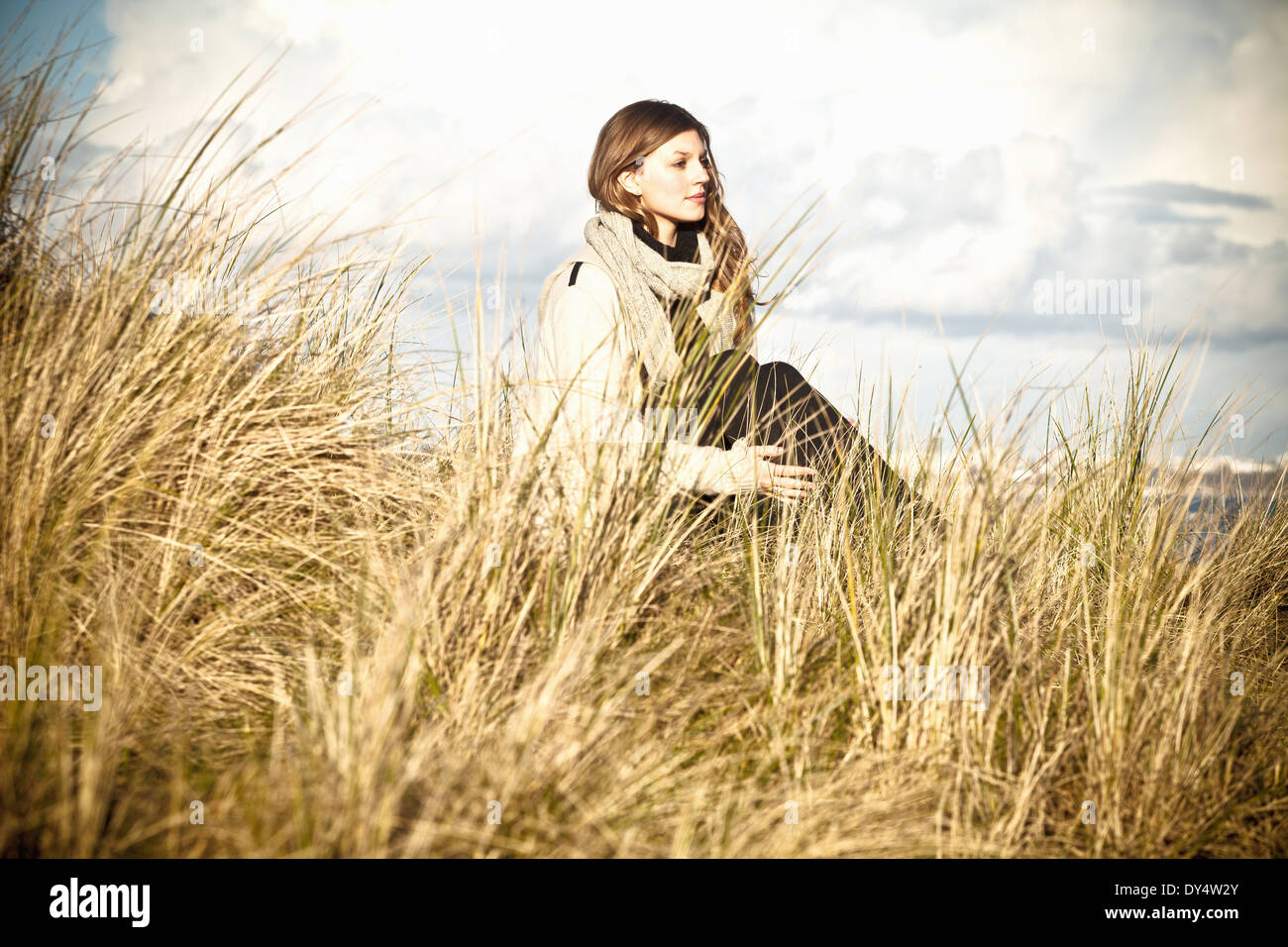 Young woman sitting in sand dunes, Bournemouth, Dorset, UK - Stock Image