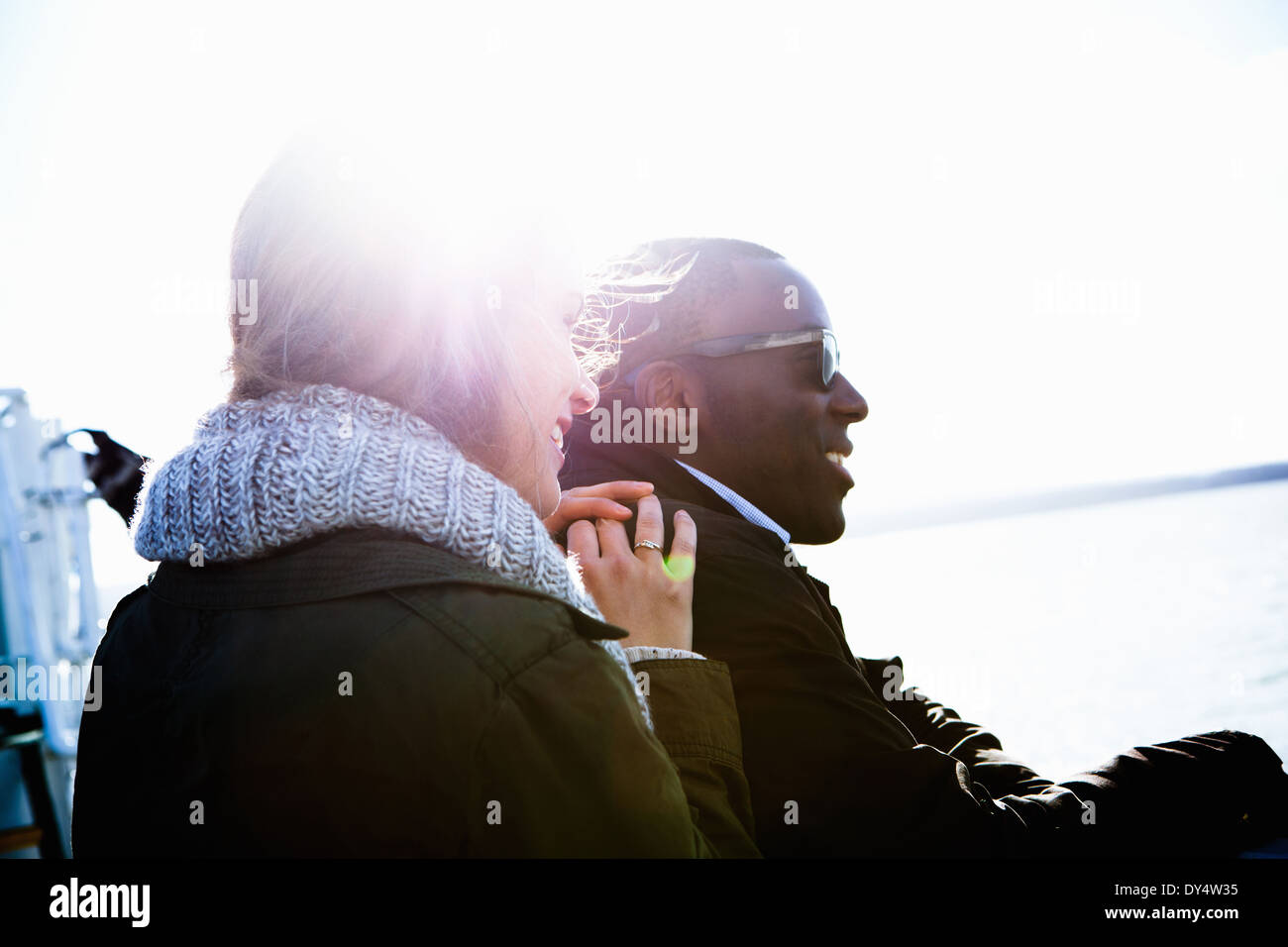 Young couple sitting outdoors in sunlight Stock Photo