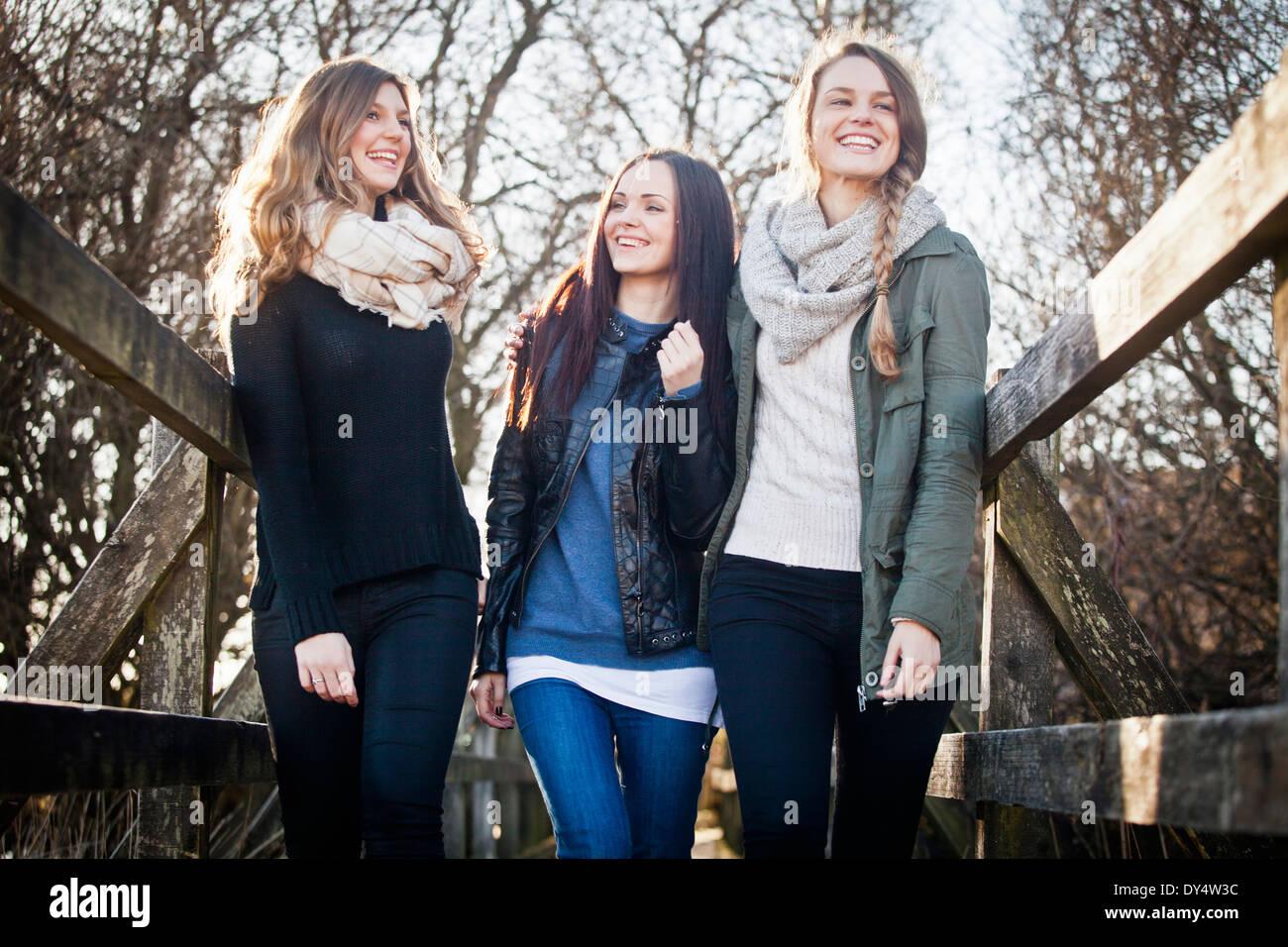 Three female friends strolling over footbridge - Stock Image