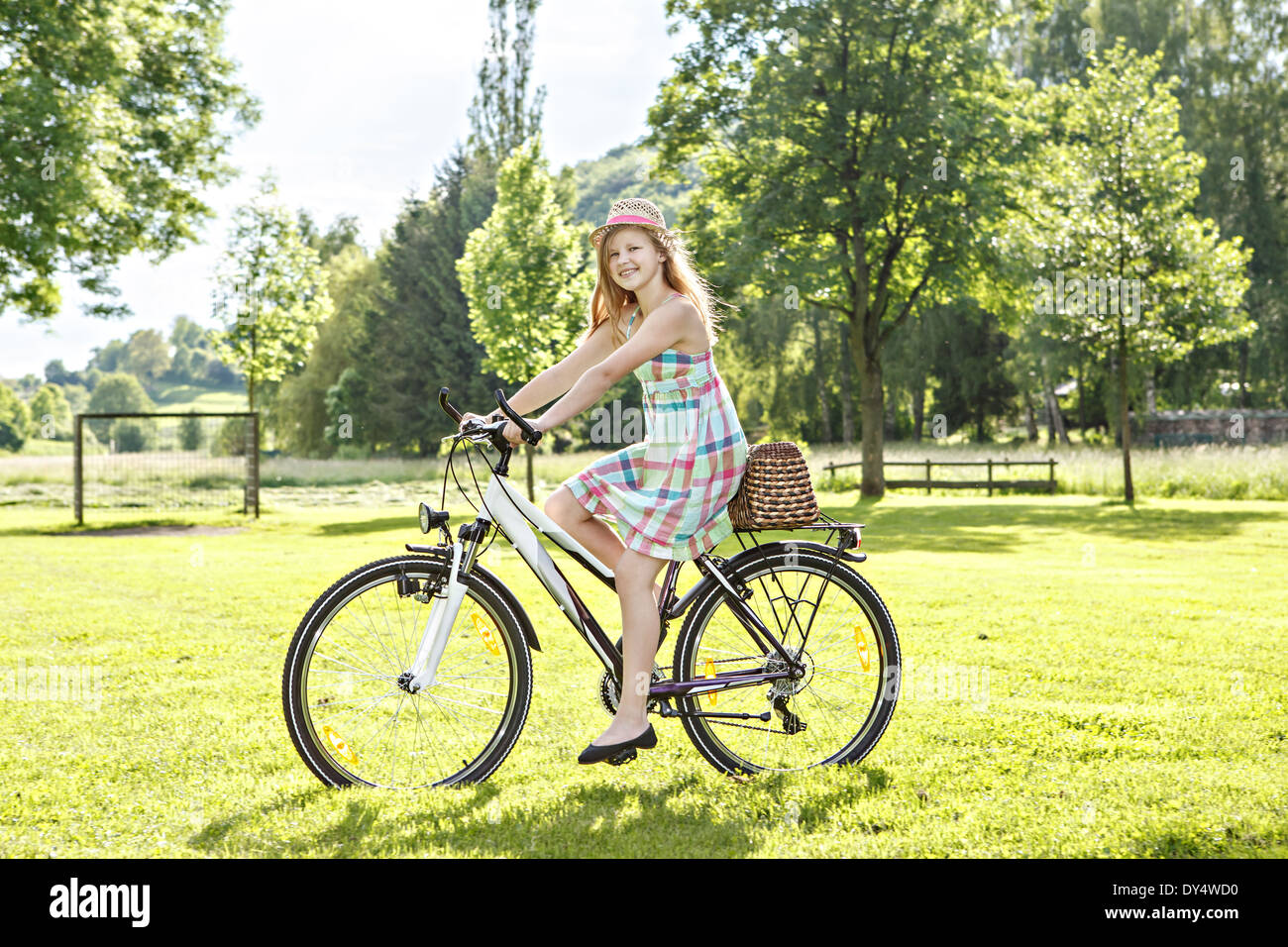 teenage girl cycling in a summerly park - Stock Image