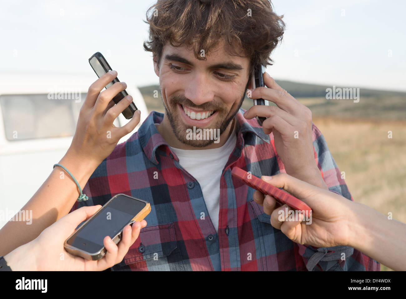 Young man on cell phone with hands holding smartphones - Stock Image