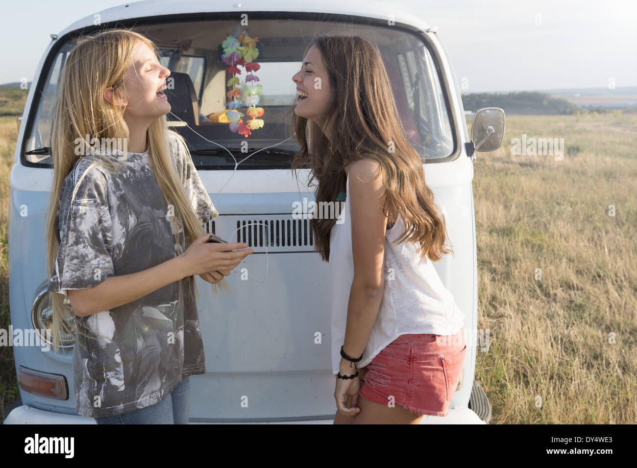 Young women listening to music by campervan - Stock Image
