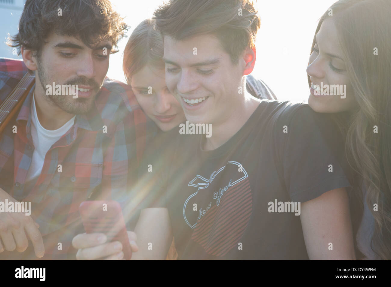 Four friends looking at smartphone - Stock Image