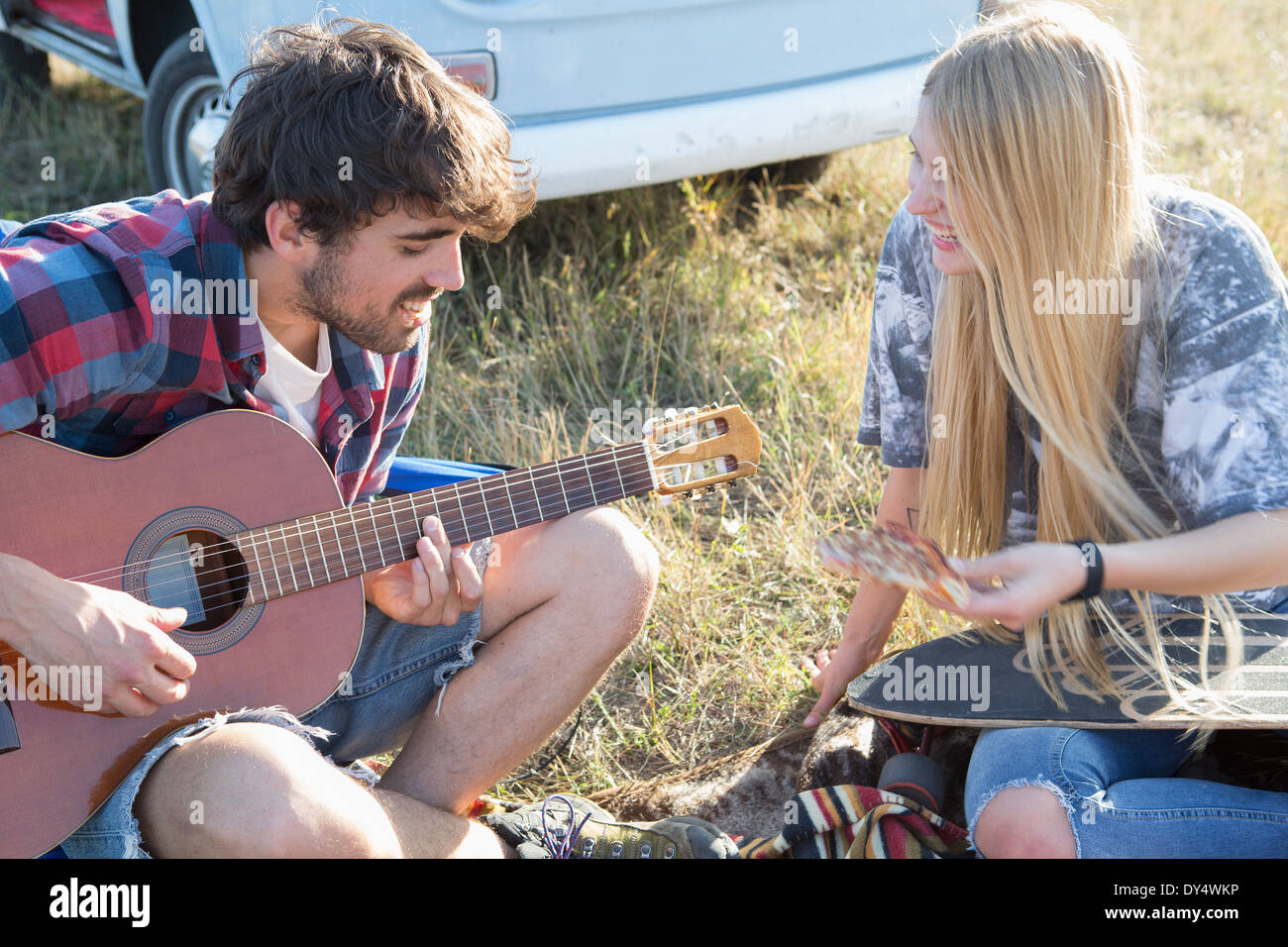 Young man playing guitar for young woman - Stock Image