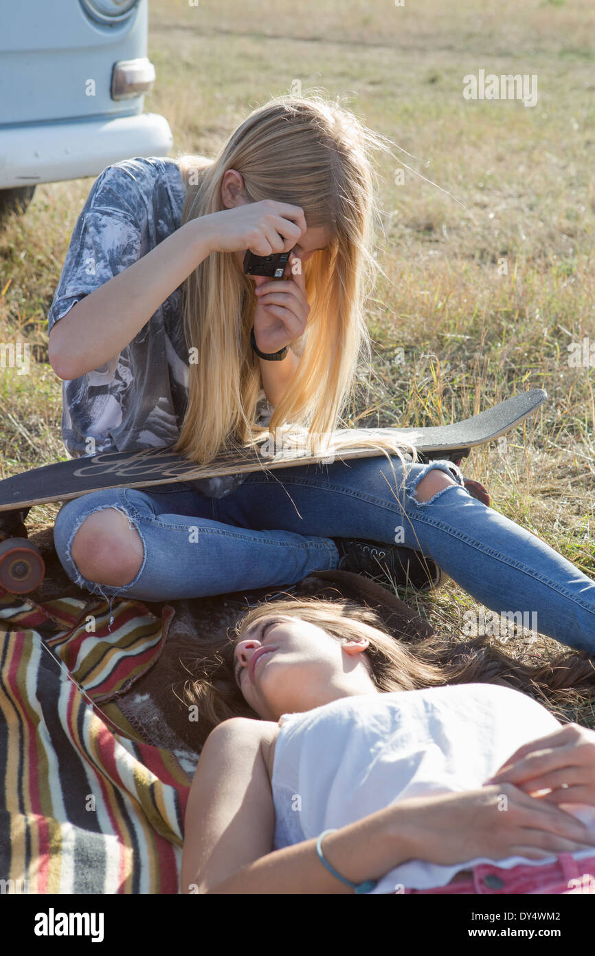 Young woman photographing friend lying on blanket - Stock Image