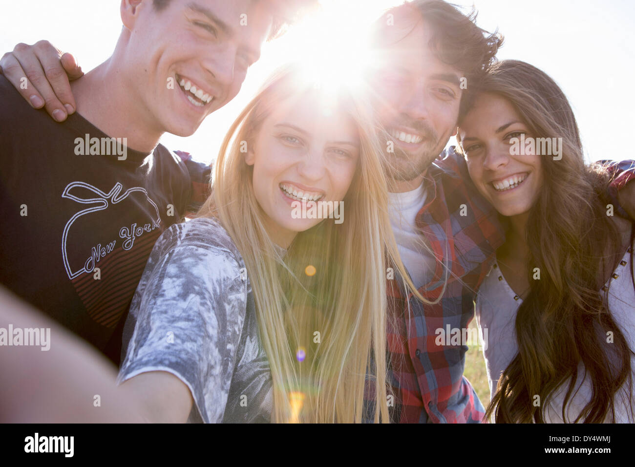 Four friends smiling toward camera - Stock Image