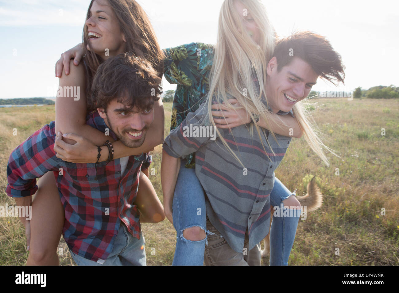 Young men giving women piggy backs - Stock Image