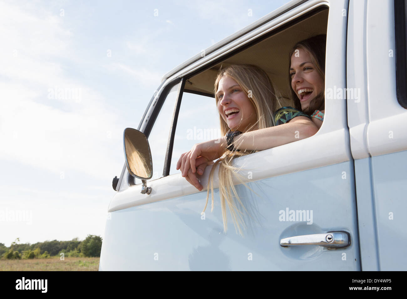 Young women looking out of campervan window laughing - Stock Image