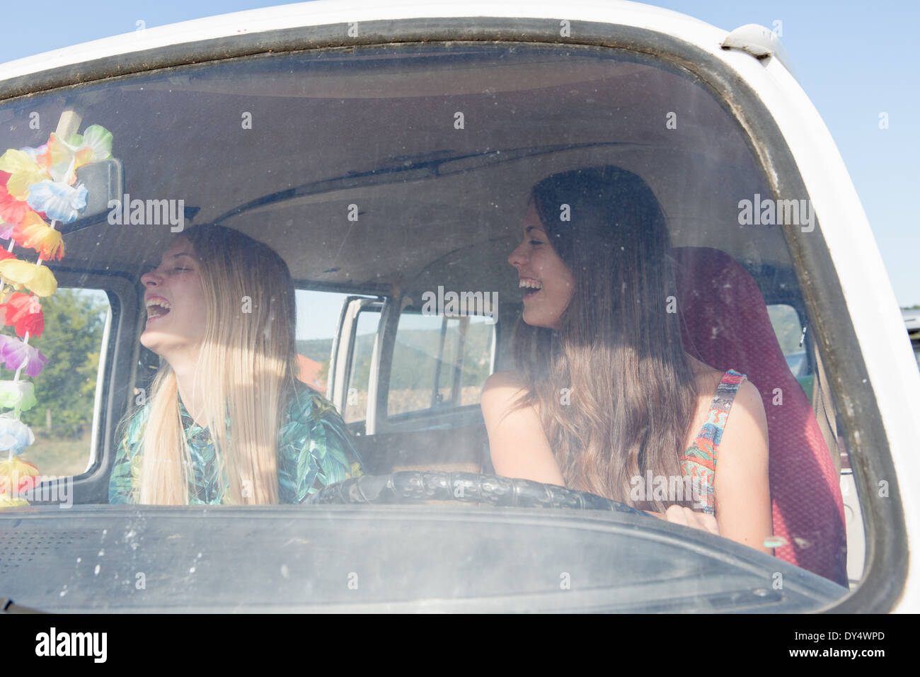 Young women inside campervan laughing - Stock Image