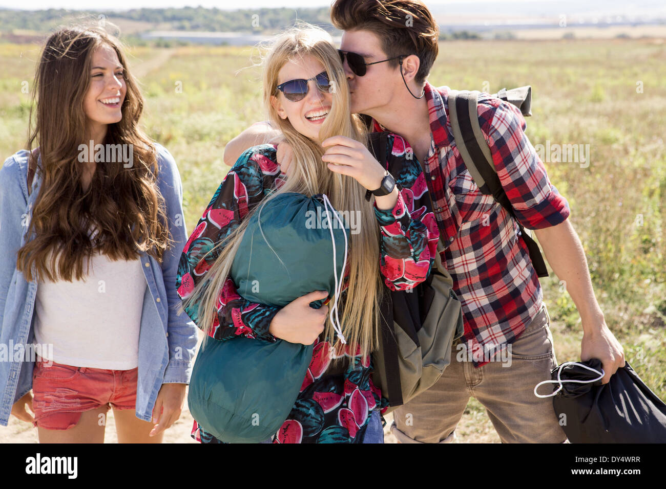 Three friends out hiking, man kissing woman - Stock Image