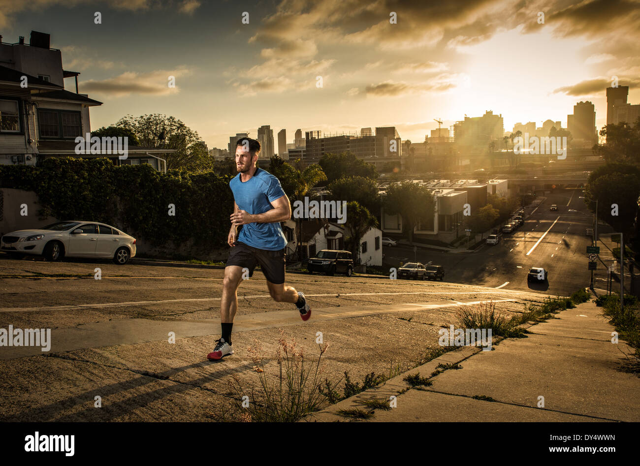 Young male runner running up a steep city hill - Stock Image