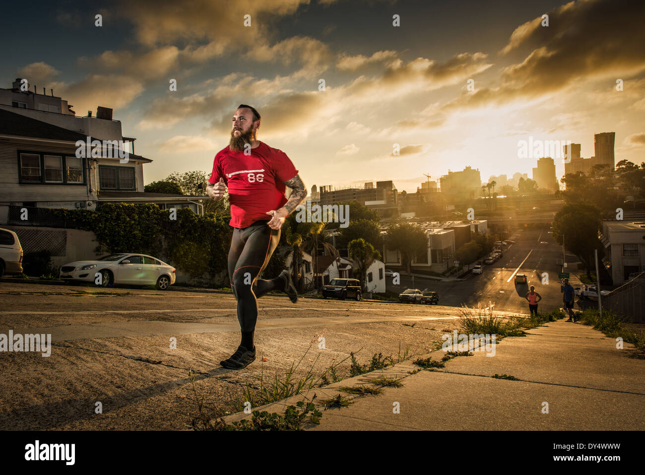 Mid adult male runner and team mates running up a steep city hill - Stock Image