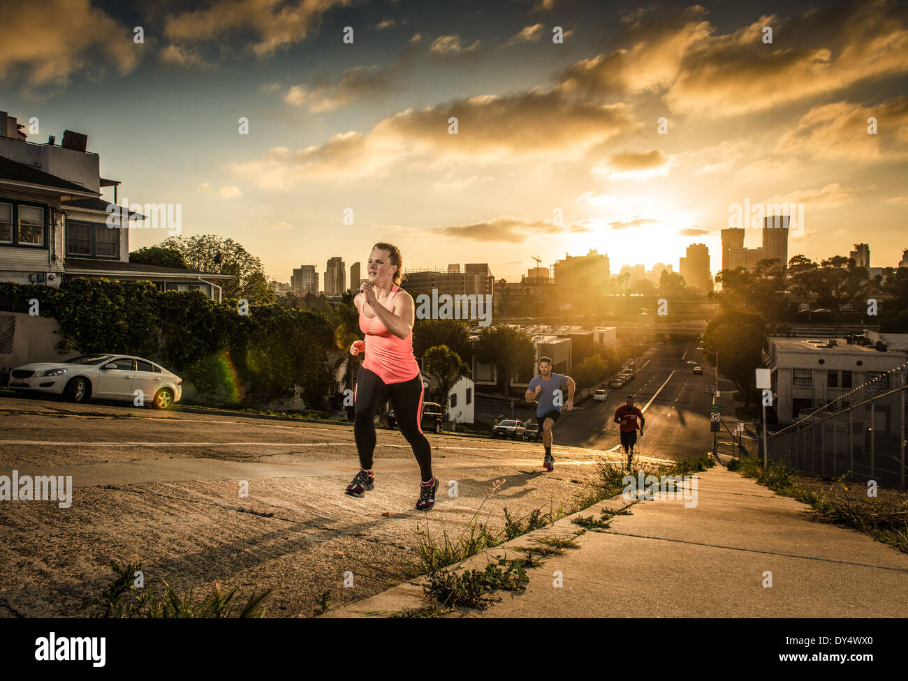 Team of runners running up a steep city hill - Stock Image
