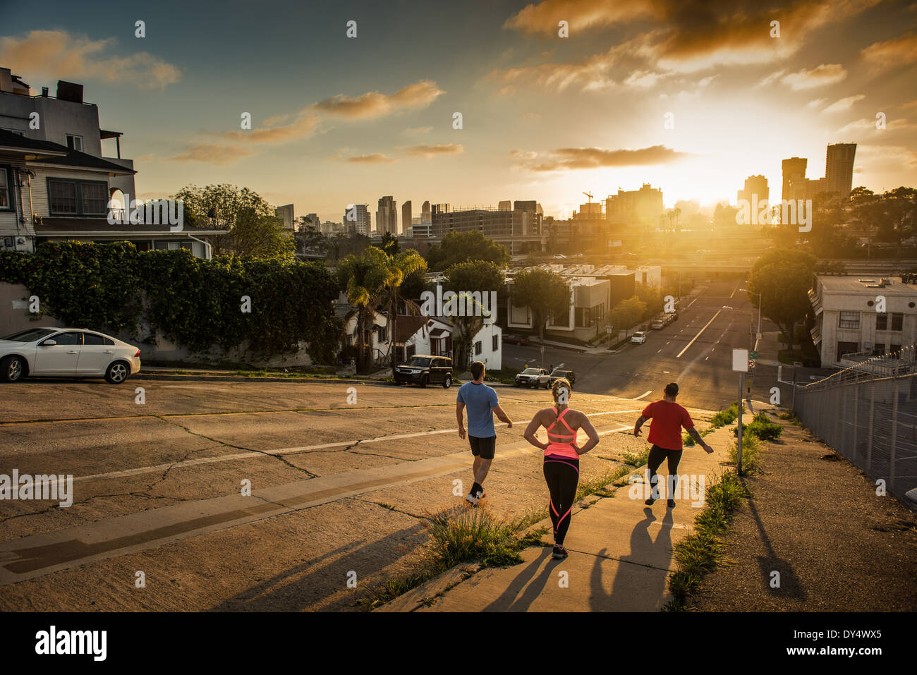 Team of runners running down a steep city hill - Stock Image
