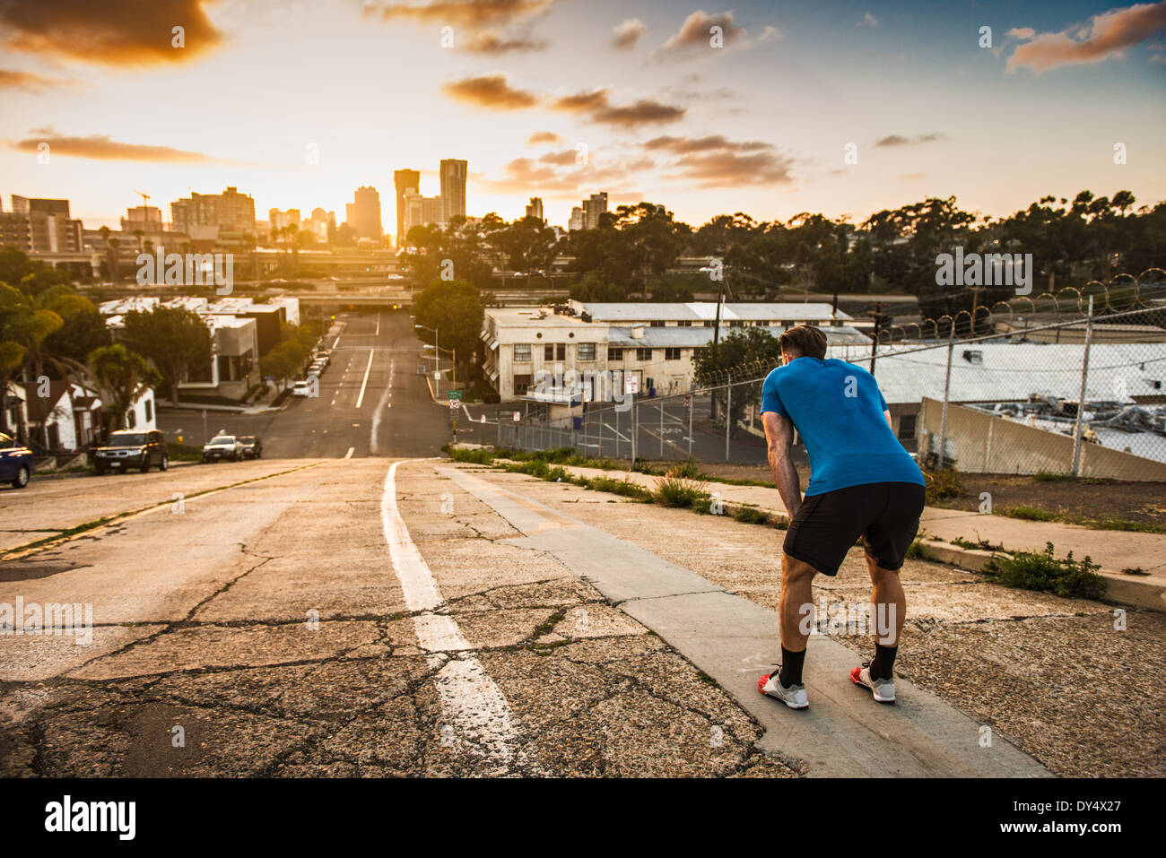 Young male runner taking a break at the top of a steep city hill - Stock Image