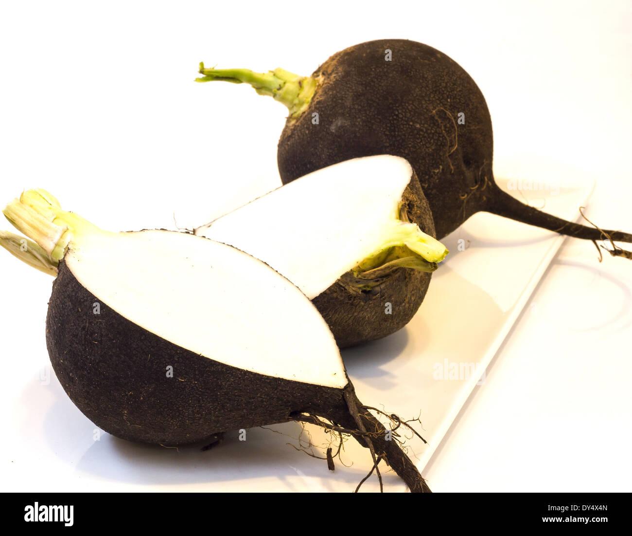 Photo black winter radish on a bright background . - Stock Image