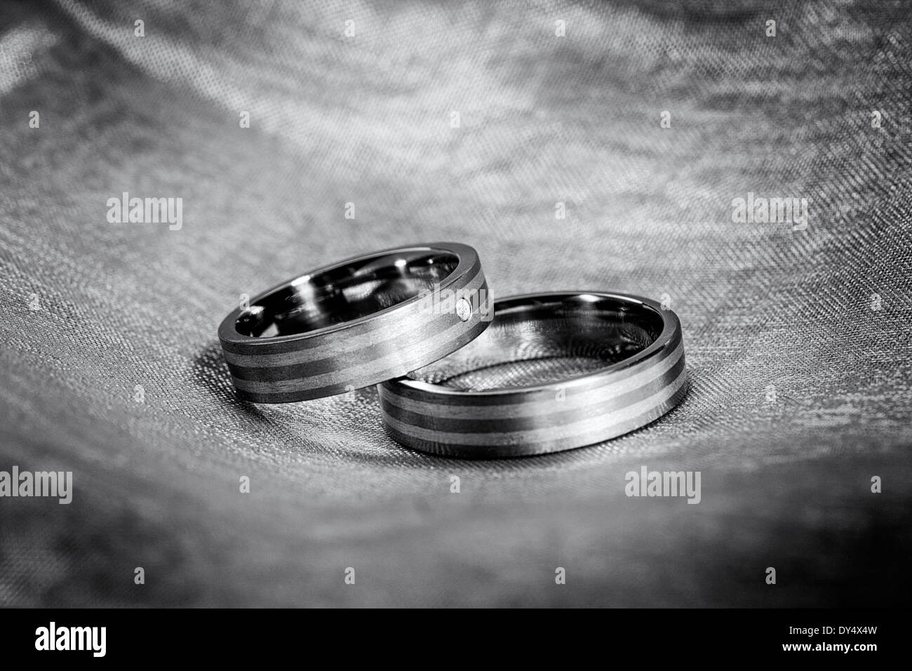 Black And White Image Of Wedding Rings On Cloth Stock Photo