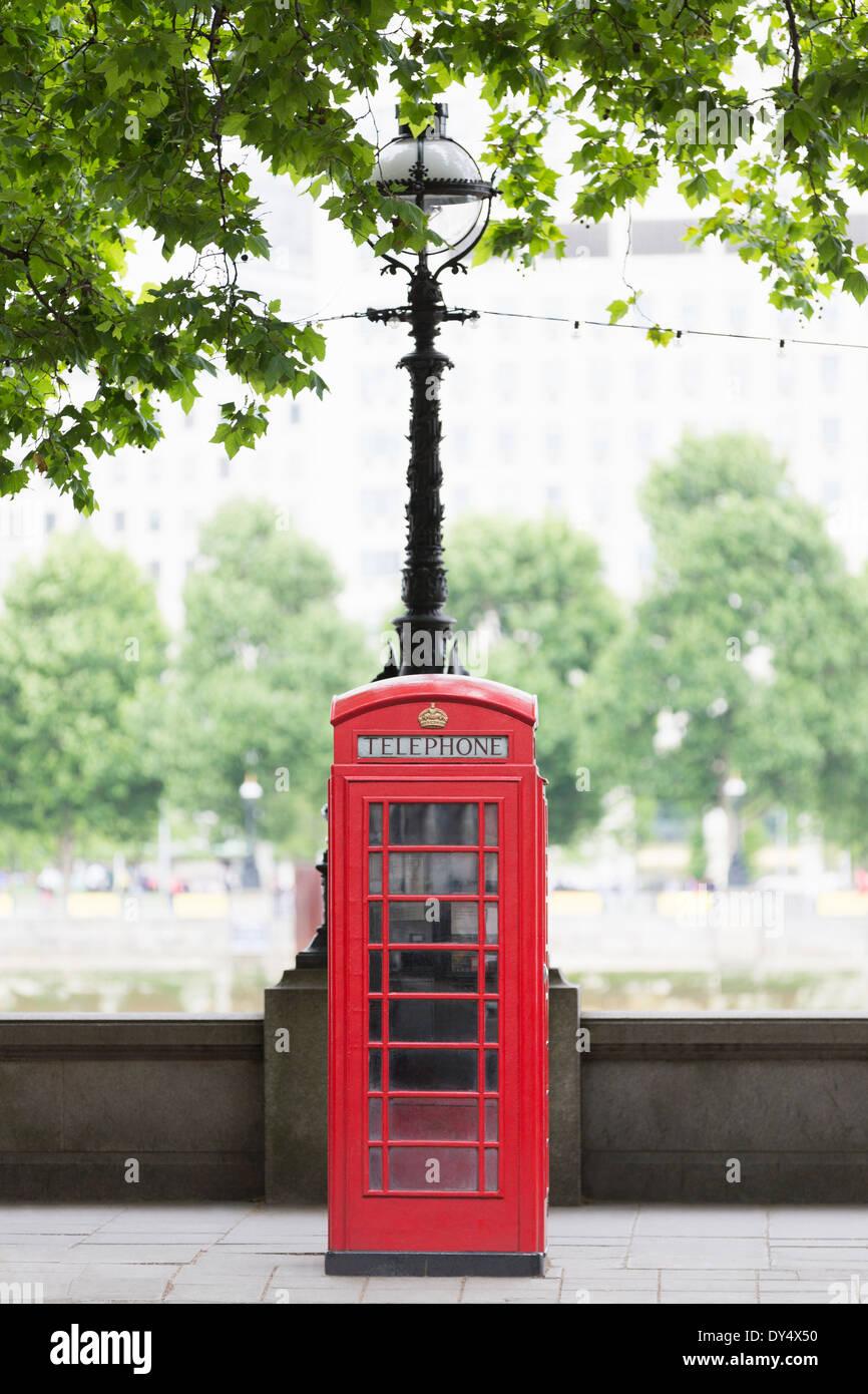 Traditional red telephone box on Embankment, London, UK - Stock Image