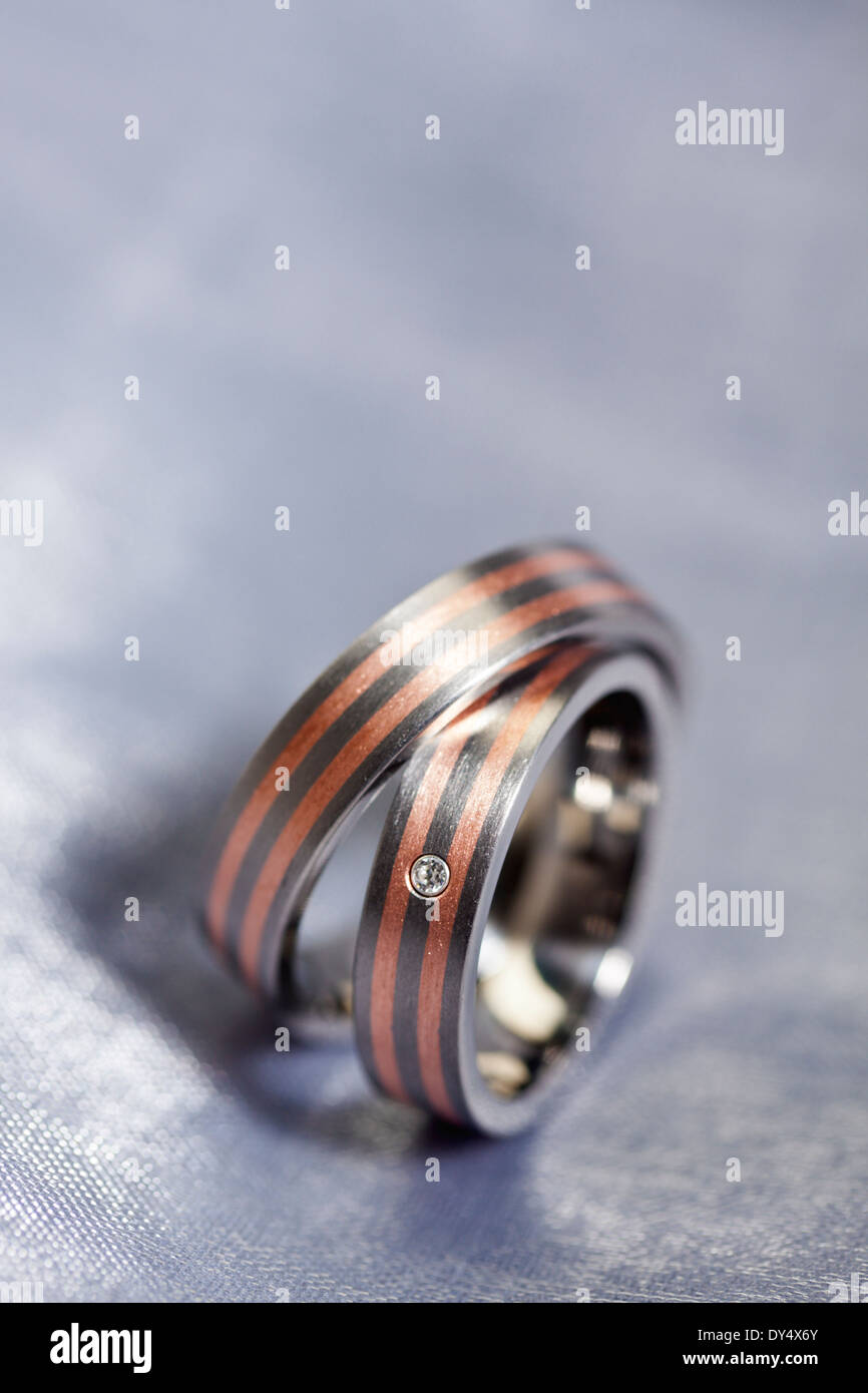 Red Gold and Platinum wedding rings on silver cloth - Stock Image