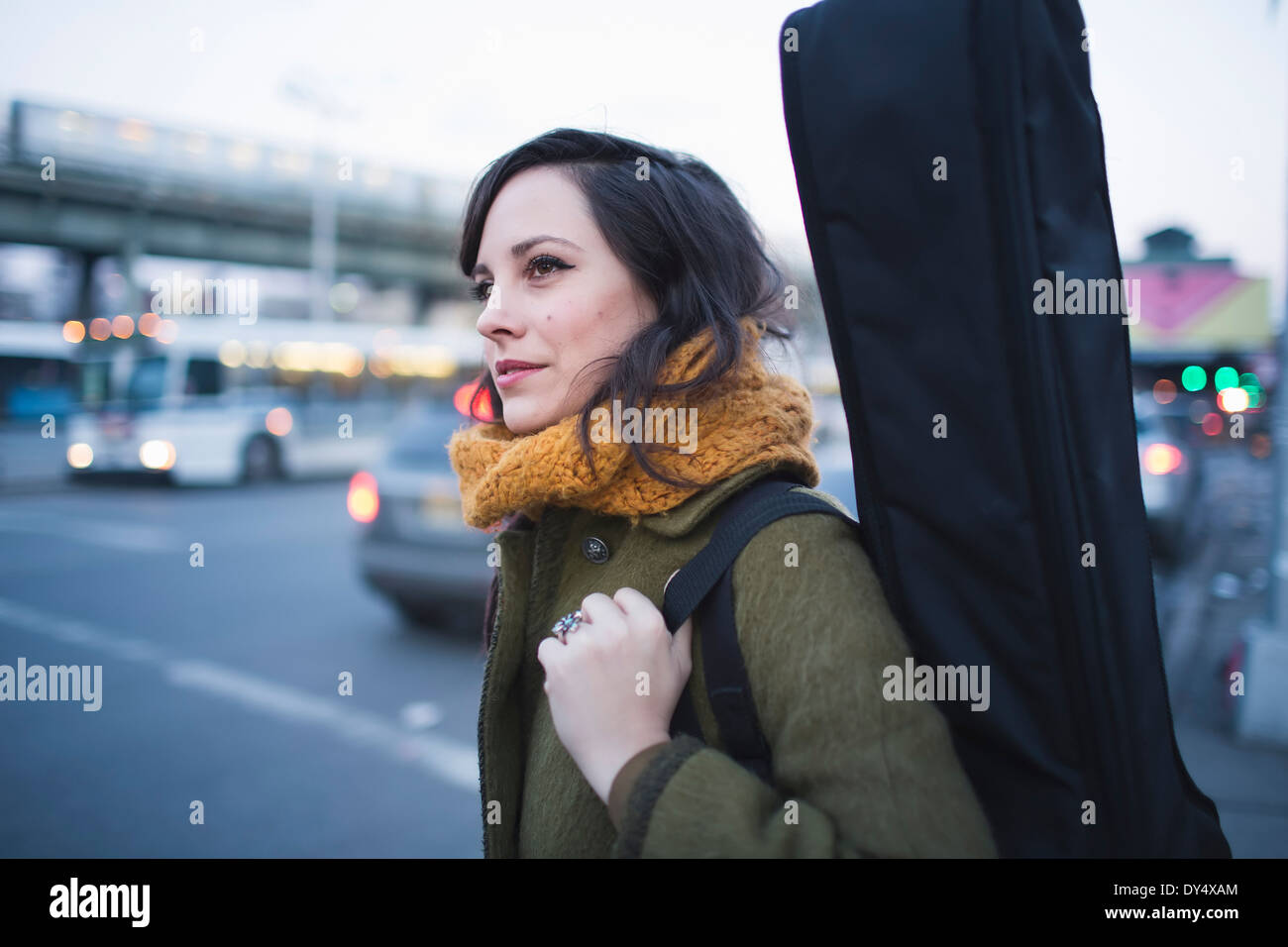 Young woman carrying guitar case - Stock Image