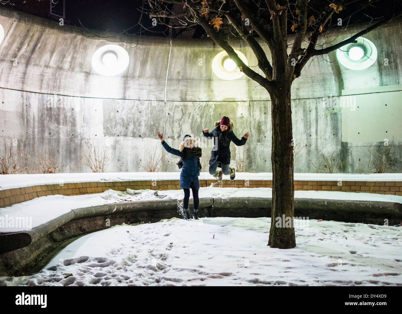 Friends jumping in snow - Stock Image