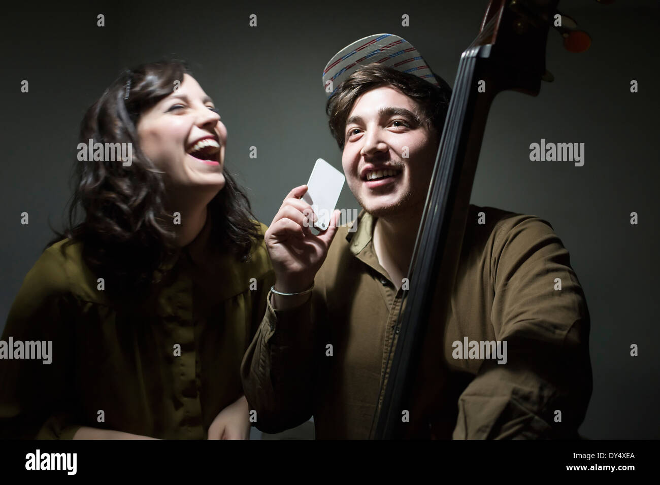 Young musicians with double bass and smartphone, laughing - Stock Image