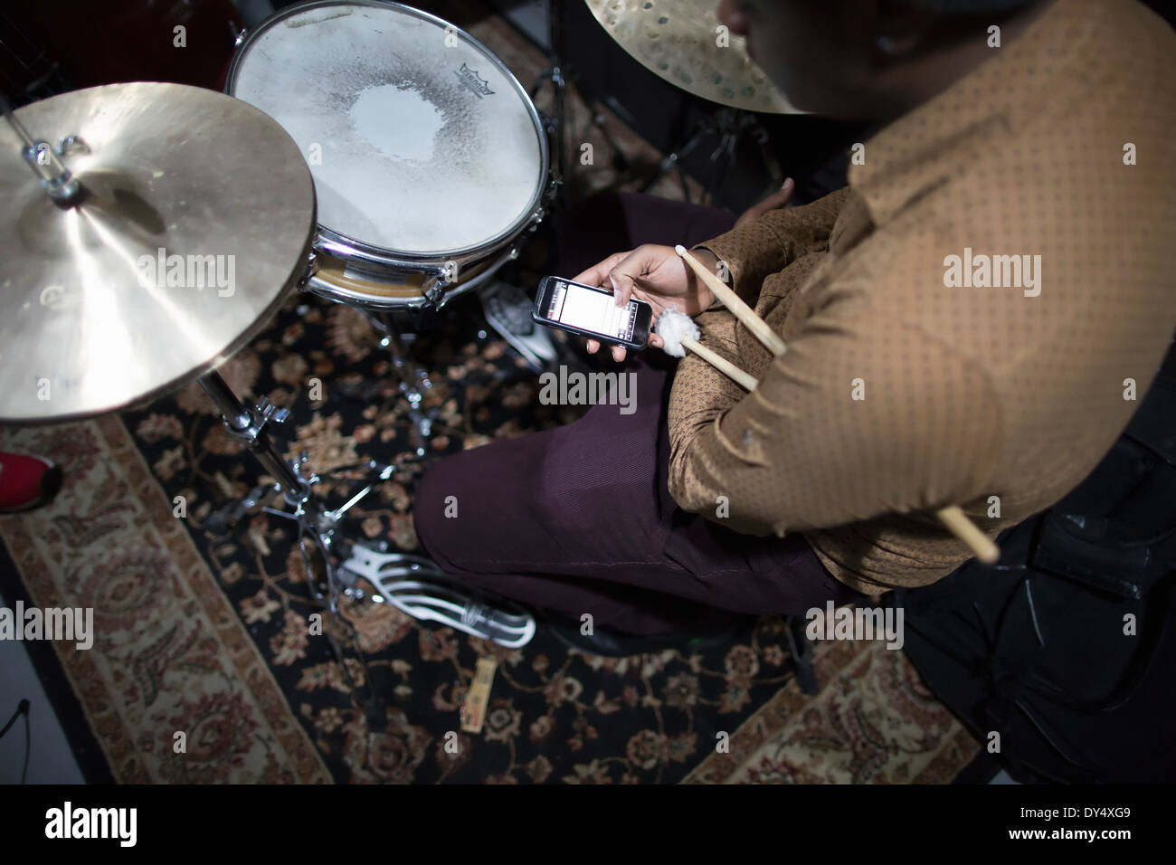 Drummer sitting at drum kit, using smart phone - Stock Image