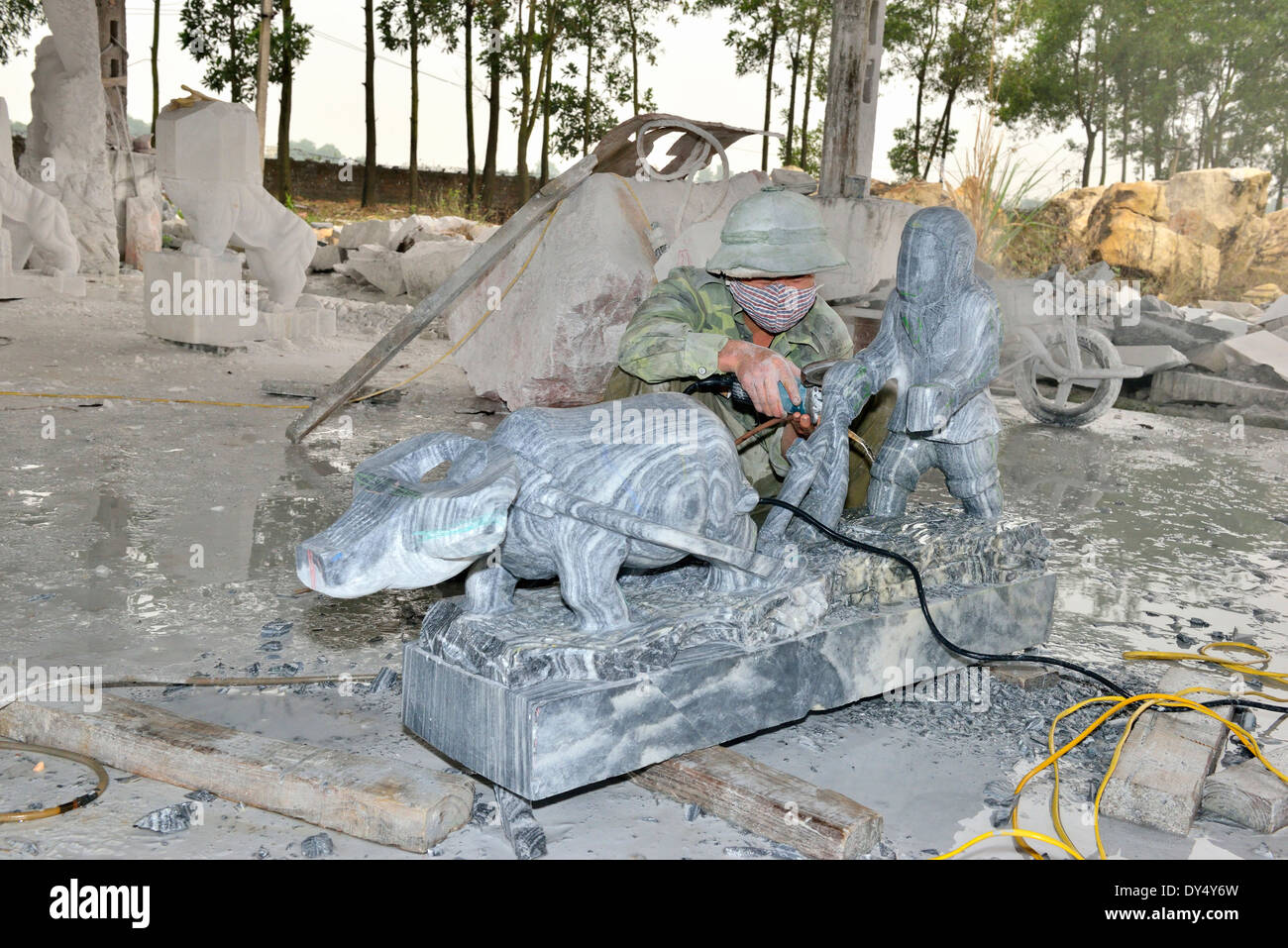 Stone cutter cutting rock with grinder and carving into large ornaments for tourists to buy at the Hong Ngoc Handicraft center. - Stock Image