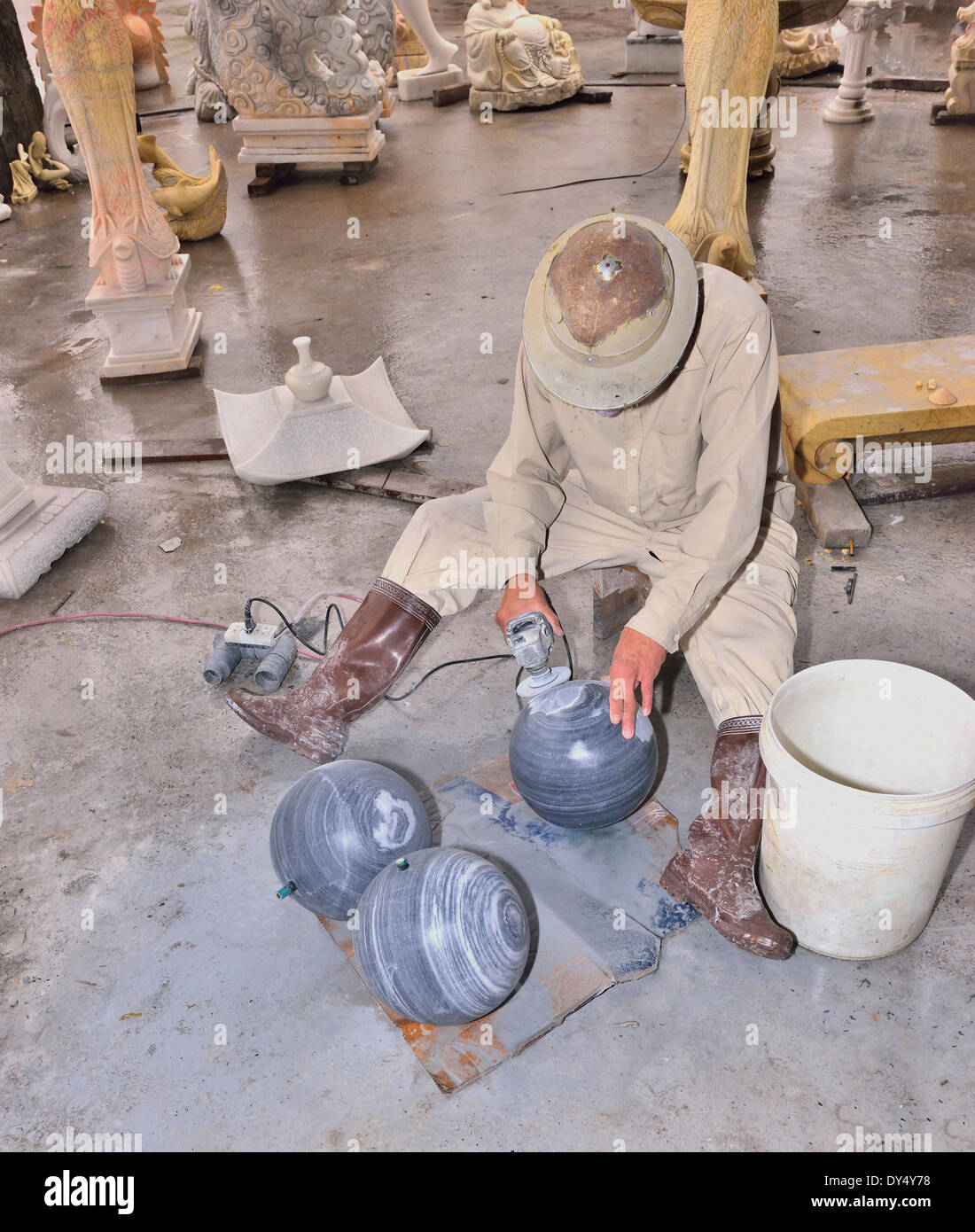 Stone cutter shaping rock with grinder and carving into small ornaments for tourists to buy at the Hong Ngoc Handicraft center. - Stock Image