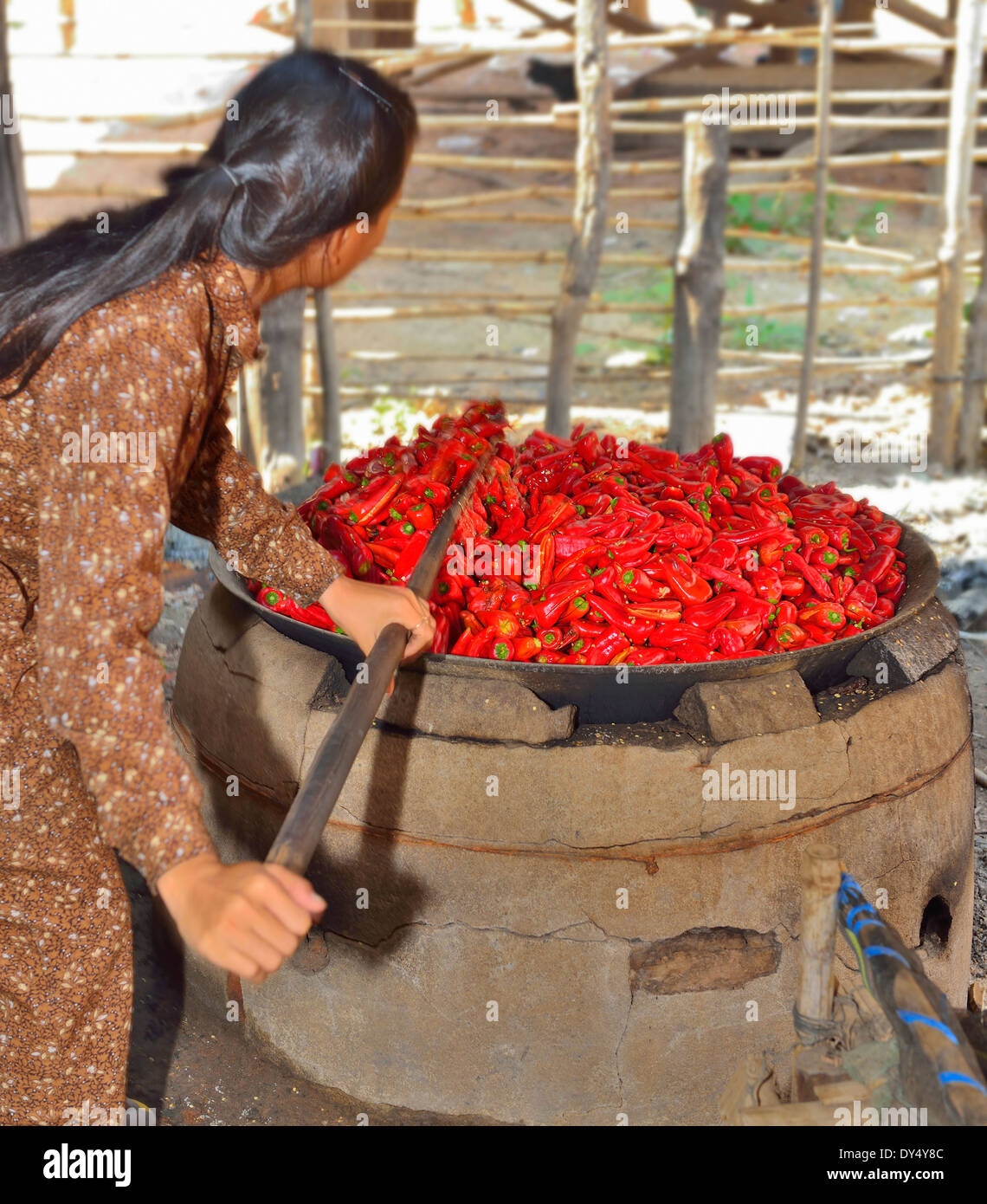 Cambodian woman cooks chili peppers in an open fired cauldron in the preparation of chili peppers a cottage industry Stock Photo