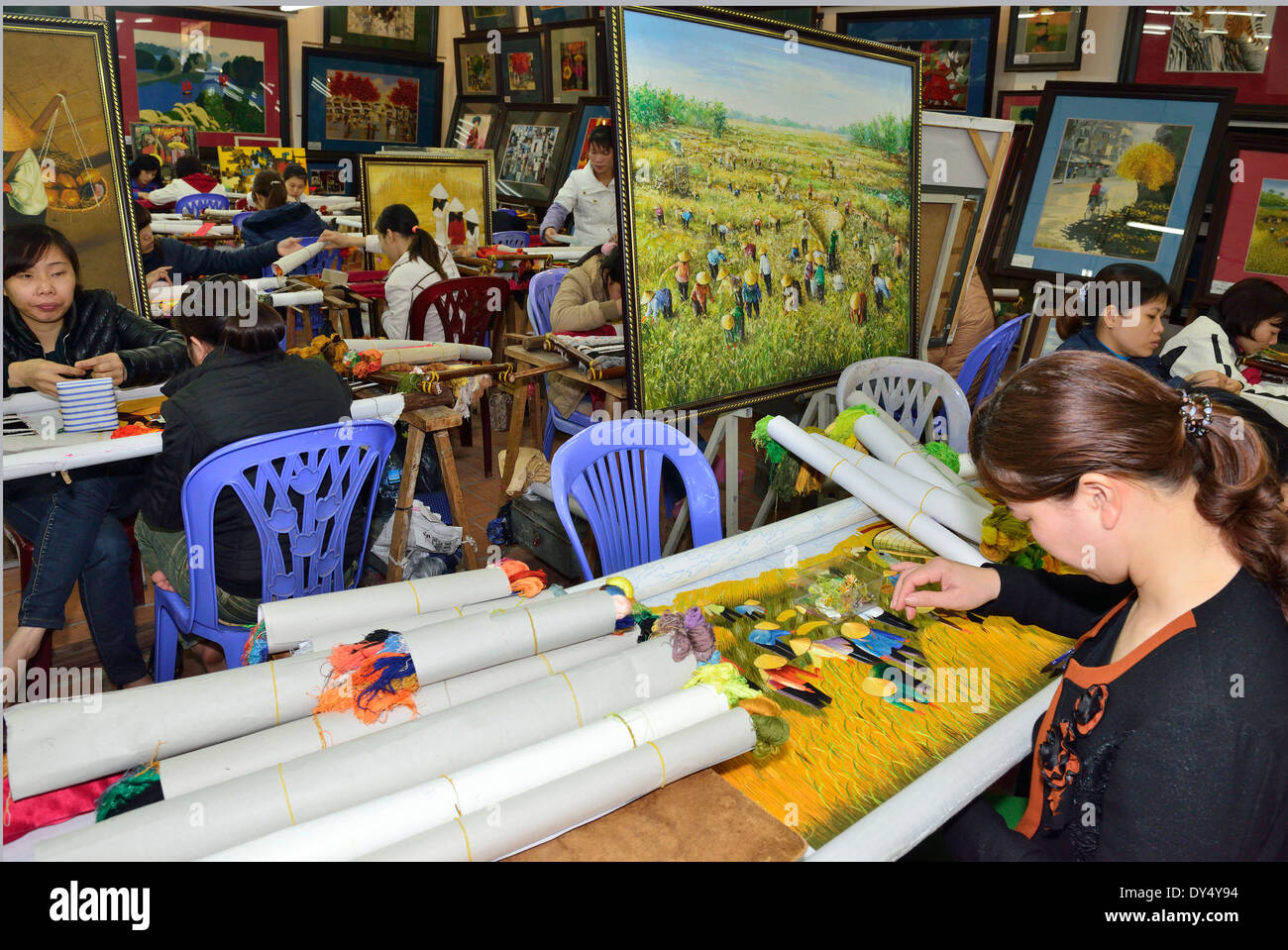 Women workers in Hong Ngoc Handicraft center Vietnam, embroidering from a painting as the template. - Stock Image