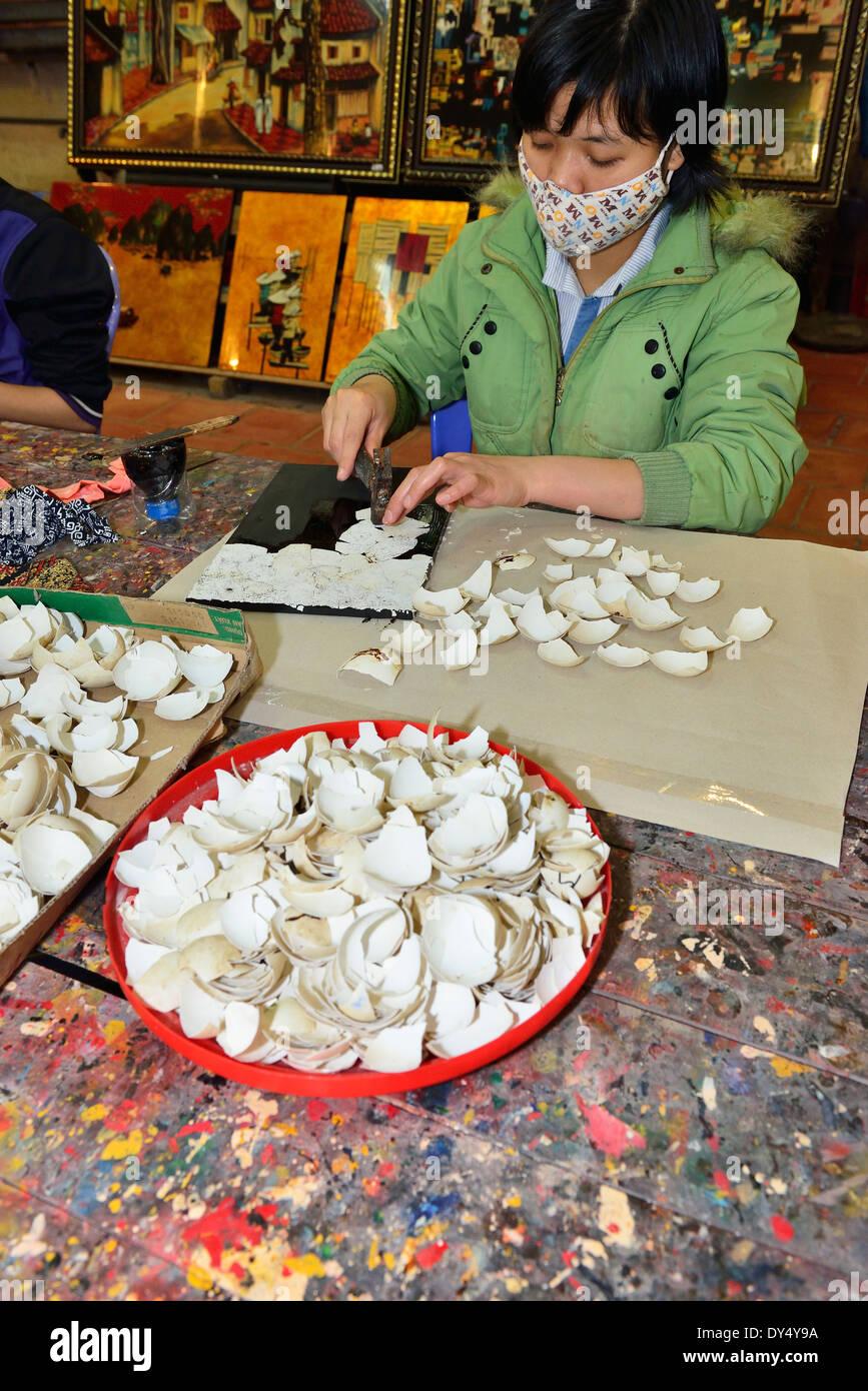 Skilled craft Vietnamese making a mosaic  from crushed egg shells at Hong Ngoc Handicraft center - Stock Image