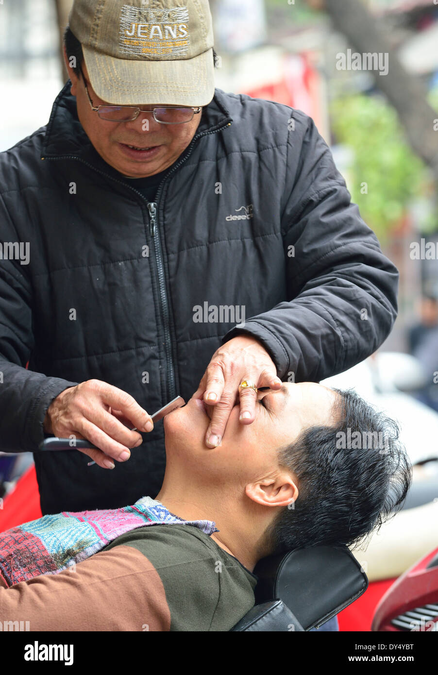 Street shaver on pavement  with customer ,Old town Hanoi Vietnam shaving his face with an open  'cut throat razor' - Stock Image
