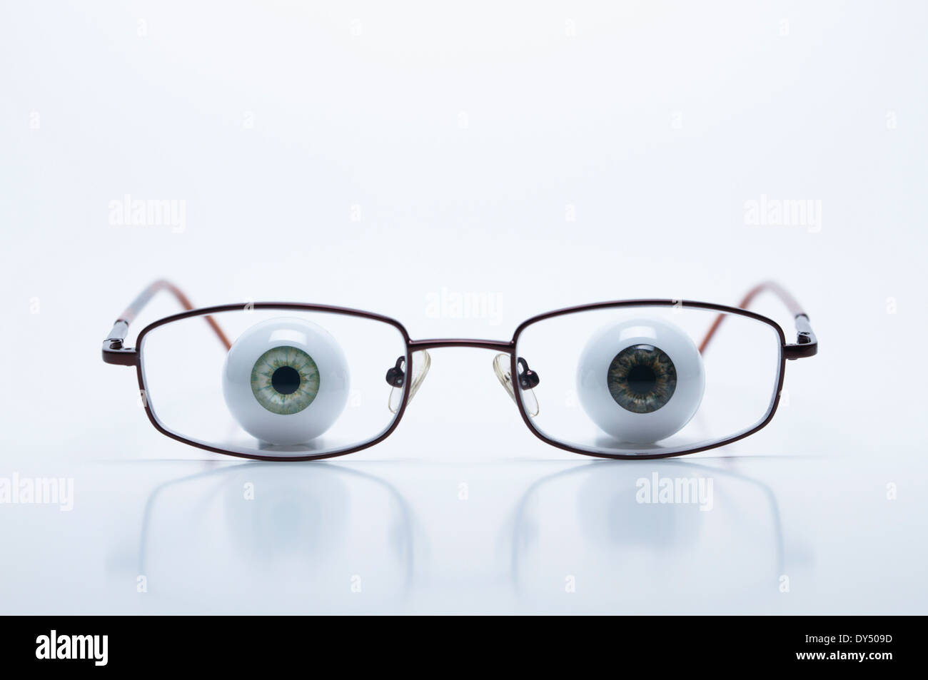 Model eyeballs behind spectacles with myopic (negative) lenses - Stock Image
