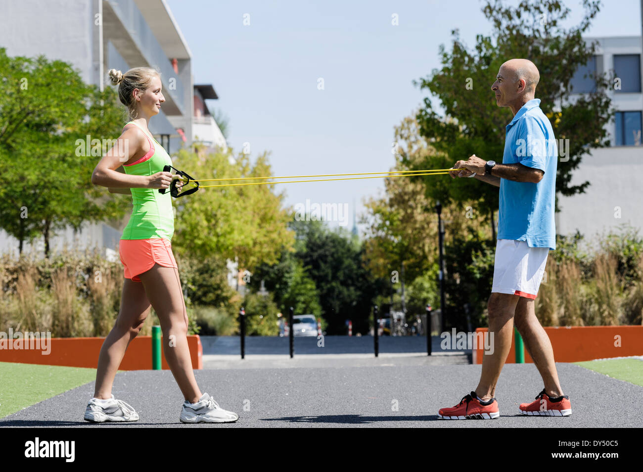 Young woman and trainer using exercise ropes in park - Stock Image