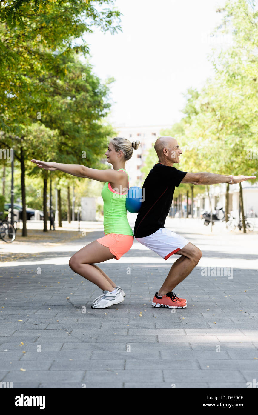 Young woman and trainer using exercise ball in park Stock Photo