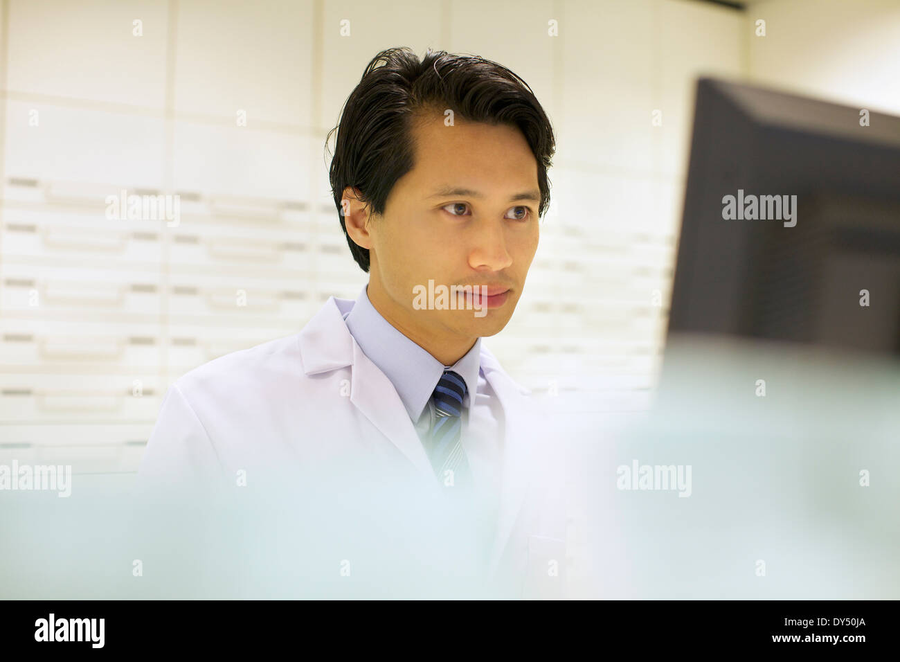 Pharmacist working on computer in pharmacy - Stock Image
