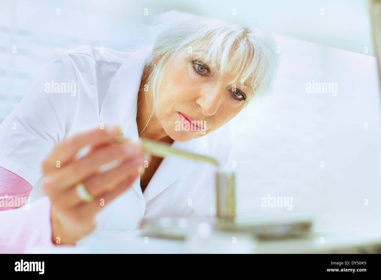 Female pharmacist weighing medicines for prescription - Stock Image