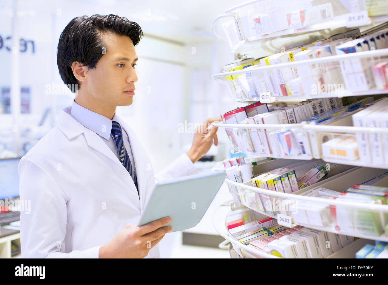 Male pharmacist stock taking in pharmacy - Stock Image