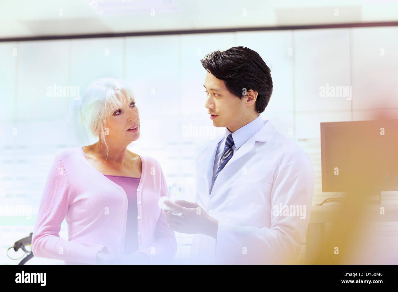 Pharmacist advising customer on medication - Stock Image
