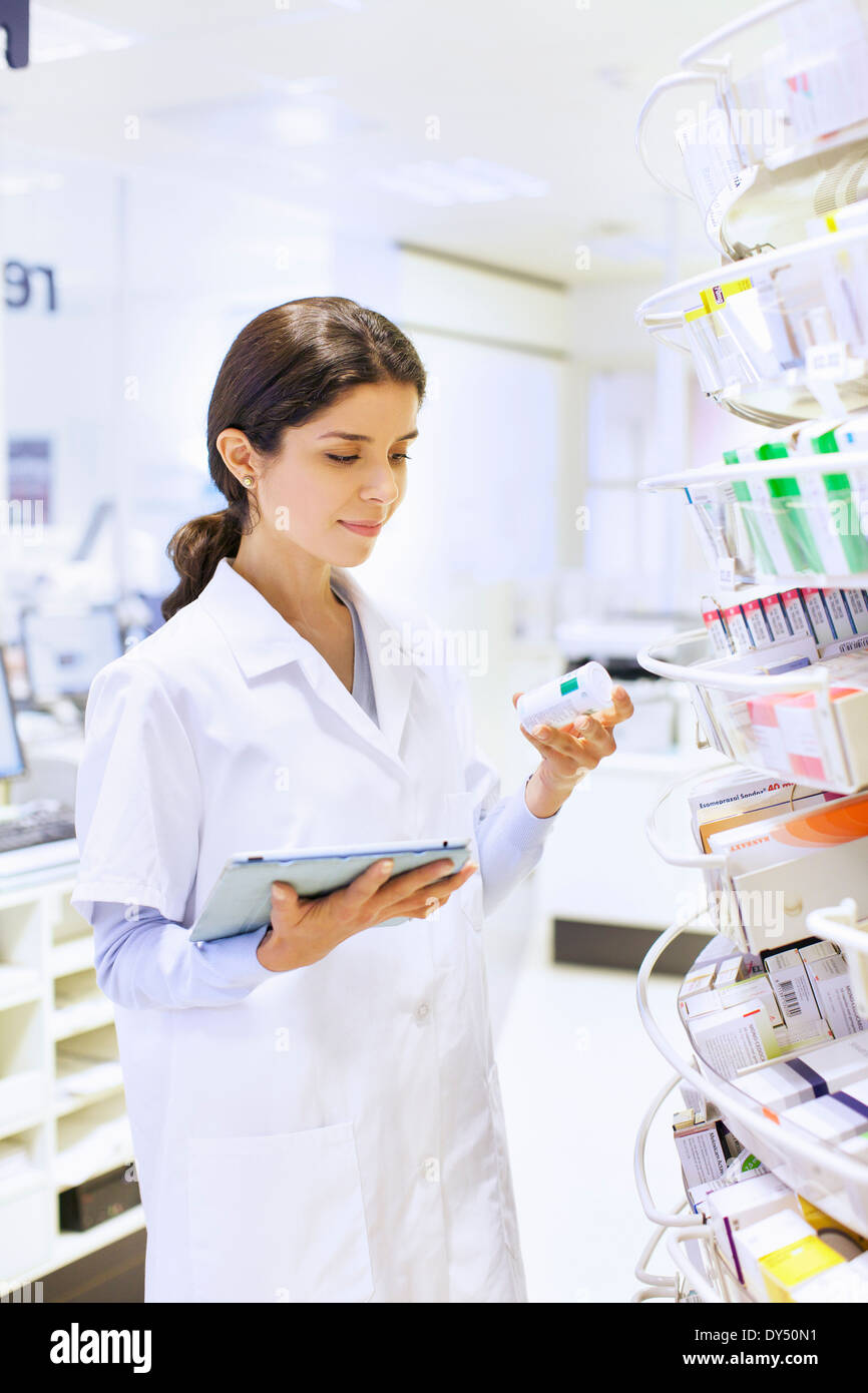 Young female pharmacist stock taking in pharmacy - Stock Image