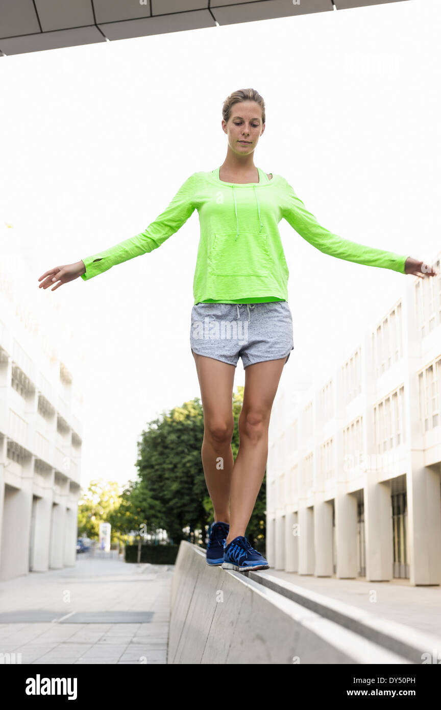Young woman walking on divider - Stock Image