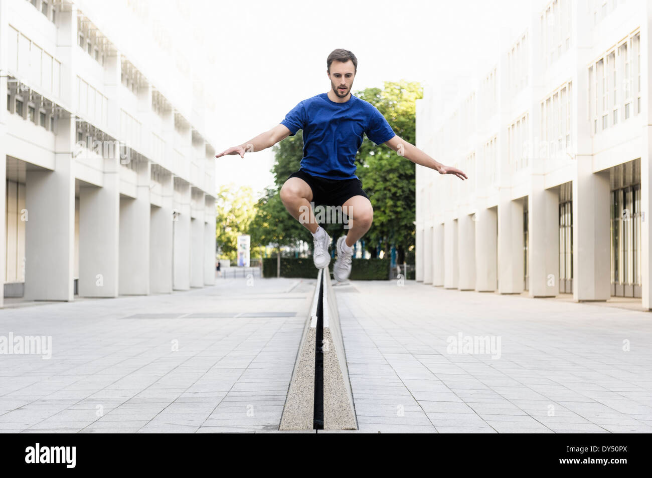 Young man jumping over divider - Stock Image